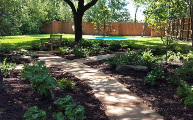 Instead of fighting with the shade in this landscape to keep trying to grow grass, which was a waste of water and fertilizer, we transformed this shady landscape into a haven for low-maintenance shade-loving plants and a place for the homeowners to cool off and relax.